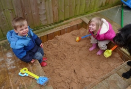 British kids - not so sunny today but still in the sand pit