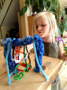 A pipe cleaner swing and person